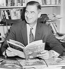 Theodor Seuss Geisel surrounded by his literary works. He holds one of his most popular, The Cat in the Hat.